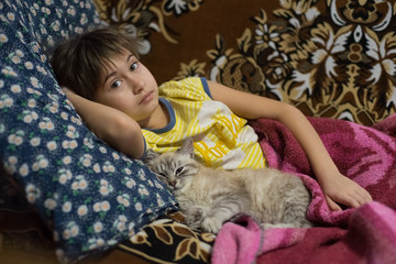 Little girl and kitten are lying on the bed. Girl is lying on a pillow and cat is lying next to her. Cat almost sleeps. Girl and kitten are looking at camera.