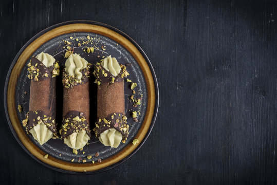 Served traditional Italian dessert cannoli with pistachios,blank space