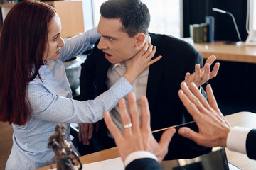 Enraged wife strangles astonished husband, sitting at divorce lawyer's table.