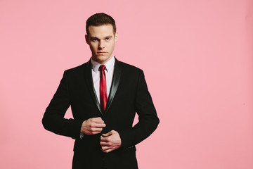 Handsome young man in black suit and tie  and hands on jacket on pink background