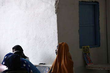 A migrant from Cameroon looks on as he protects himself from the cold inside the Juventud 2000 shelter in Tijuana