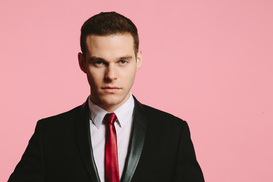 Close up portrait of a handsome young man in black suit and tie looking at camera on pink background