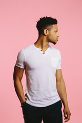 A profile Portrait of a cool African American guy in white shirt looking to the side on pink background