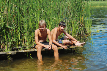 Two boys, a teenager rest on the river bank, on a hot day