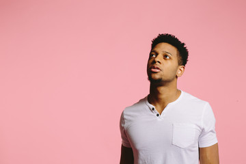 Portrait of a cool African American guy in white shirt on pink background