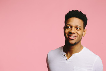Portrait of a smiling African American guy looking sideways on pink background