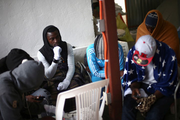 Migrants from Cameroon gather as they protect themselves from the cold inside the Juventud 2000 shelter in Tijuana