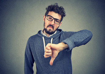 man in eyeglasses showing dislike with thumb down gesture