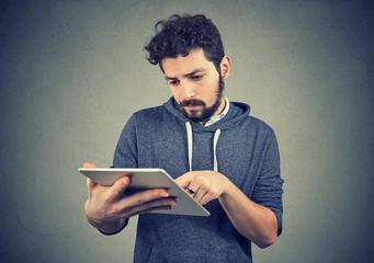 Curious man using pad on gray