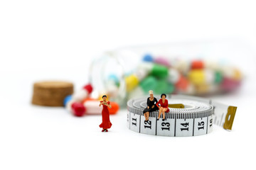 Miniature people : woman sitting on tape Measure with slim body woman and drug background.