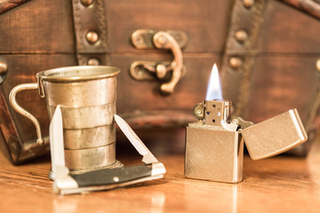 A vintage lighter in a old style scene with an old antique pocket knife and an old whiskey collapsable shot glass from the early western days.