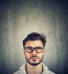portrait of a doubtful man with glasses looking up