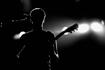 Silhouette of an unrecognizable man playing an electric guitar
