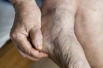 Closeup of elderly hand massaging foot