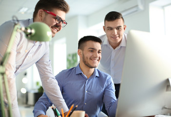 Young men working in office