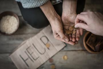 Woman giving money to poor female beggar, closeup