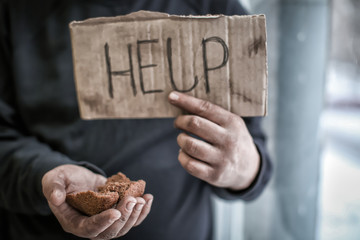 Poor man holding piece of cardboard with word HELP and bread, closeup