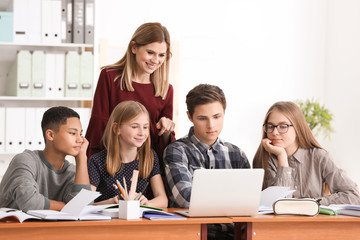 Group of teenagers doing homework with teacher in classroom