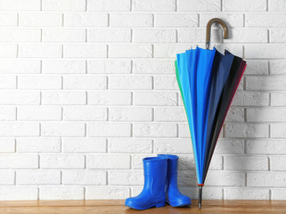 Stylish rainbow umbrella and rubber boots near brick wall