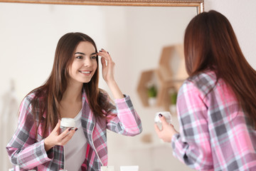 Young woman applying face cream in front of mirror in bathroom