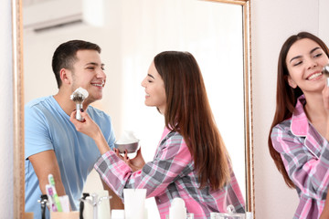 Young woman helping her boyfriend shaving in bathroom
