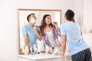 Young man shaving and his girlfriend cleaning teeth in bathroom
