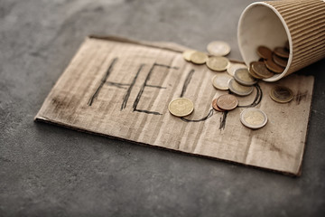 Piece of cardboard with word HELP and coins on grey background. Poverty concept