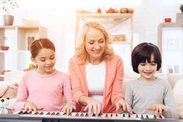 Beautiful elderly woman teaches small grandchildren to play synthesizer.