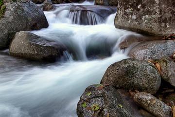 WATER FLOWING BETWEEN THE ROCKS