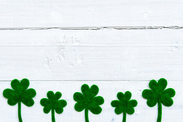 Happy St Patricks Day message and a lot of green paper clover leaf on white wooden background