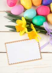Easter Eggs and Daffodil Flowers on Rustic White Board Background with blank card with room or space for your words, text, copy, or design.  Vertical photo from above with looking down view