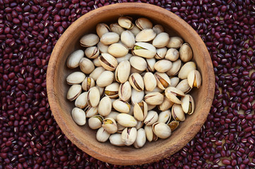 pistachios in wooden bowl on red bean background