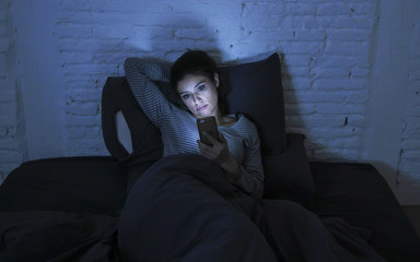 portrait of young beautiful latin woman using mobile phone late night sleepless lying in bed in the dark in smartphone and internet dating app addiction