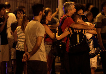 People react next to the crime scene where Rio de Janeiro city councilor Marielle Franco was shot dead in Rio de Janeiro