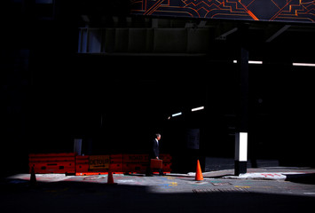 A man carrying a case walks past a building under construction on an autumn day in the central business district of Sydney