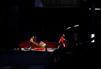A worker pushes a trolley loaded with goods past a construction site in the central business district of Sydney