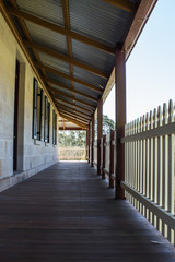 Outdoor verandah patio deck of sandstone brick cottage with picket fence in sunshine