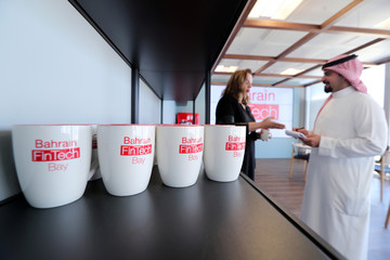 Coffee mugs with logos of Bahrain FinTech Bay are on display as staff chat in its office in Bahrain Bay, Manama