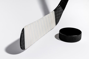Ice hockey stick and puck on isolated white background, equipment for hockey player in winter game season.