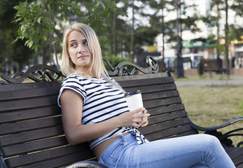 young beautiful girl drinks coffee in the park, beautiful blonde is resting in the park with a glass of coffee, coffee with her, working break.