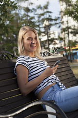 young beautiful blond girl talking on mobile phone and smiling, beautiful blonde doing selfie on mobile phone, talking on phone in park