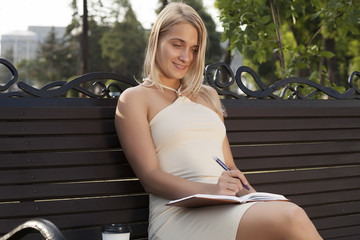 young beautiful blonde girl writes, pensive portrait, beautiful female student in park, education, female student at break in park, beautiful young girl writes letter and smiles
