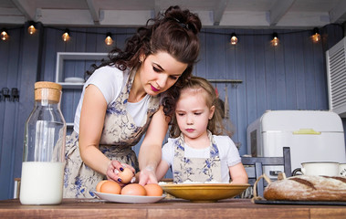 Mom and daughter are cooked together from flour, eggs and milk