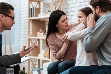 Young couple tries to reach out to small daughter at session with family psychologist.