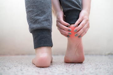Young woman massaging her pain ankle. Health care concept