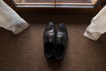 Black men's leather shoes on a brown background. Wedding details.