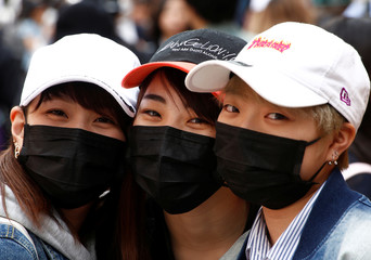 Japanese women wearing masks to prevent pollen allergy and for fashion, pose for photographs at Harajuku shopping district in Tokyo