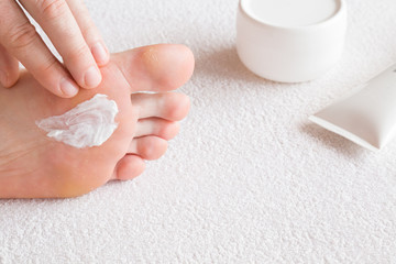 Groomed man's hands applying feet moisturizing cream. Bare feet on the white towel. Cares about clean and soft legs skin. Healthcare concept.