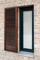 Blinds in modern window, Detail on modern brick facade with wooden window with shading elements, Contemporary narrow window with metal parapet