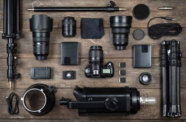 Set of the camera and photography equipment (lens, tripod, filter, flash, memory card, hard desk, reflector) on wood desk. Professional photographer accessories background.